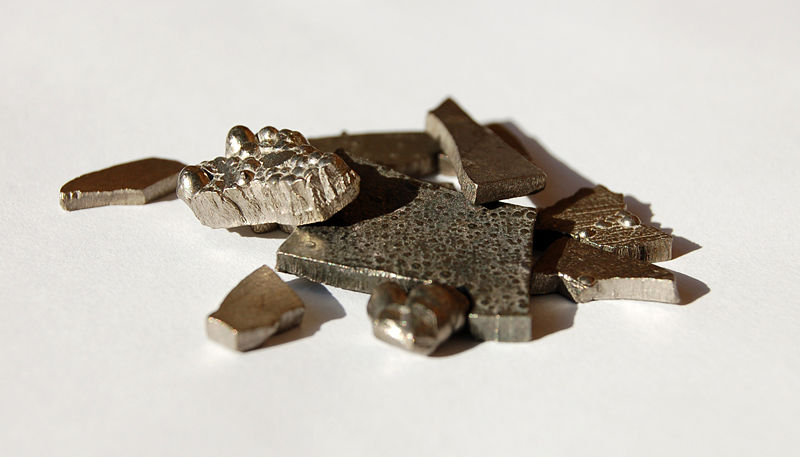Chunks of solid cobalt can be seen in this photo. The different shaped pieces sit on a table which also serves as a white background.