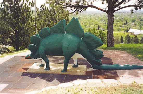 This picture shows a Stegosaurus model found at a dinosaur park. Stegosaurus were herbivores and featured rows of unique bones along their back and tail.