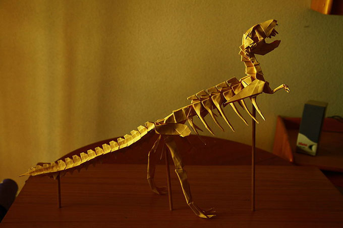 This photo shows an impressively constructed Tyrannosaurus rex origami model standing on a desk.