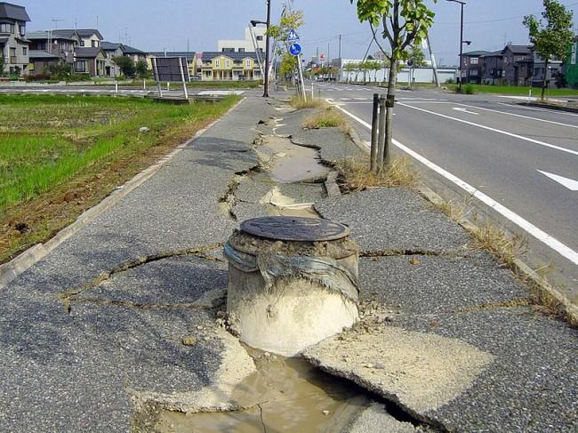 This photo shows just how much damage a strong earthquake can cause. The concrete pavement beside the street has been torn in two with a large crack down the middle.