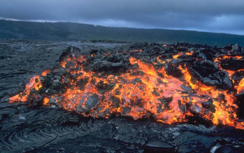 A close up photo of a lava flow as it makes its way from a volcano crater after a recent eruption.
