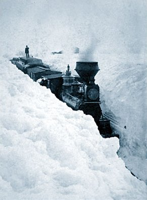 An old photo showing a train stuck in a huge snow blizzard. A man stands on one of the back carriages as the train remains stuck in the deep snow.