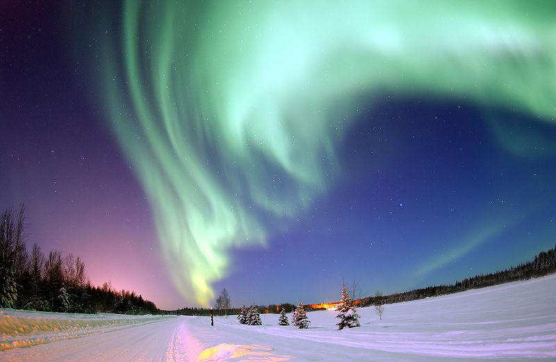 The aurora borealis (also known as the northern lights) is a spectacular light display that can be seen at night in regions near the North Pole (auroras can also be seen near the South Pole). Auroras occur because of charged particles that come from the Sun, these particles sometimes hit the Earth but we are protected by the Earth's magnetic field. However, there are weak spots in the Earth's magnetic field near the polar regions, this is where the charged particles react with particles in the air and create the aurora borealis, an amazing natural phenomenon. This incredible photo of the northern lights was taken near Bear Lake, Alaska.