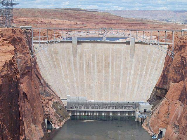 A front on photo of a massive dam built part way along a river. This giant man made structure in the Glen Canyon of USA holds back a large volume of water and is designed to remain strong for many years.