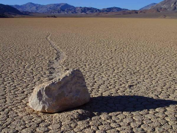 A single rock breaks up the desolate monotony of a desert landscape. The heat dries up any liquid that emerges from the ground or skies before it has a chance to help create visible life forms.
