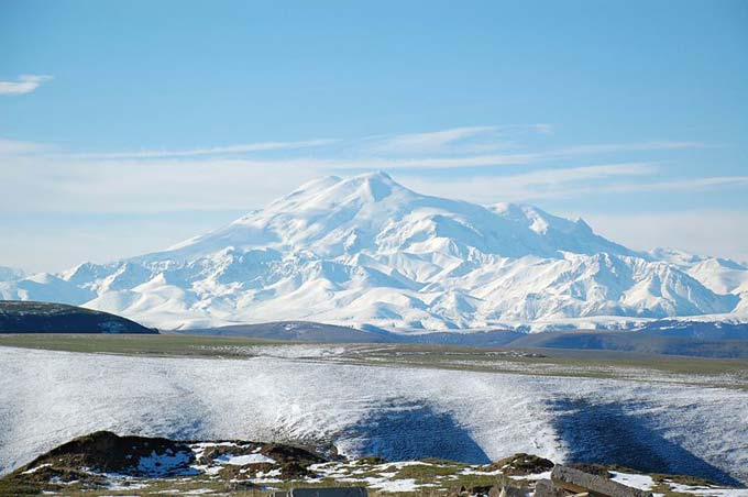 This is a beautiful photo of Mount Elbrus, the tallest mountain in Russia and all of Europe. The snow dusted mountain is an inactive volcano which has had no recorded eruptions. Mount Elbrus is 5642 metres (18510 feet) in height.
