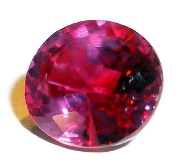 An attractive photo of an expertly cut ruby. This is an expensive kind of rock that is not commonly found. Set against a white background this ruby stands out, shining brightly as it reflects the light in a number of directions.