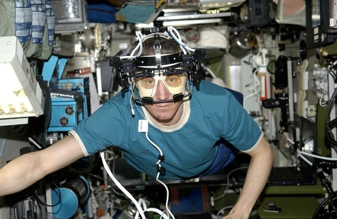 An astronaut experiments in gravity free space with an eye tracking device. The complicated equipment rests on the astronauts head as he floats around the shuttle.