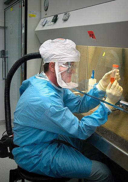 This photo shows a medical scientist hard at work doing research in a laboratory. He is wearing a range of protective clothing and equipment to ensure his safety around hazardous substances.
