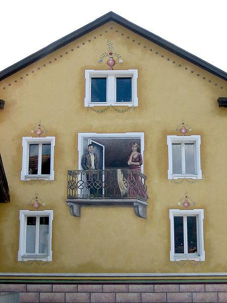 This photo shows a unique balcony facade illusion. A man and a woman appear to be standing outside on the balcony when in fact they are just drawn onto the wall of the building. There are also a number of vases that appear to be sitting on the window frames but they too are just drawn illusions.