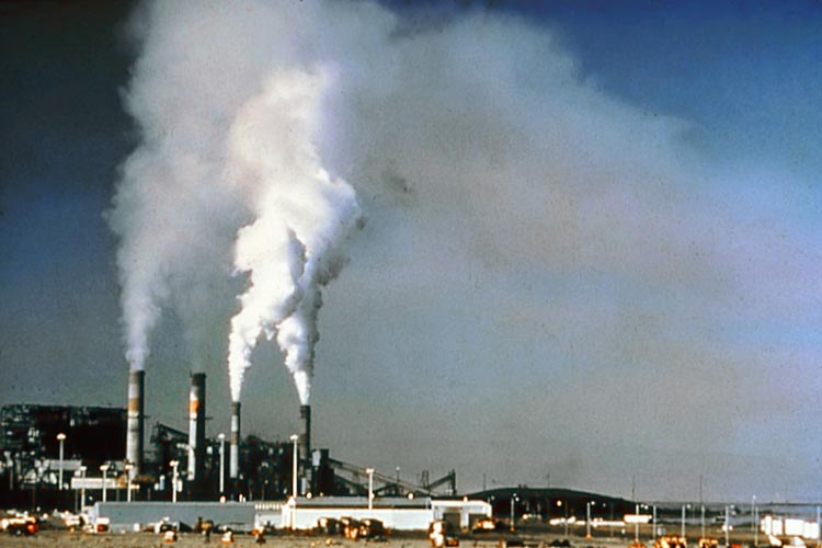 This image shows some of the air pollution problems caused by large smoke stacks before emission control standards were introduced.