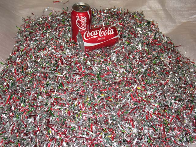 Two empty cans lie on a large pile of shredded aluminium cans which are being used for recycling purposes.
