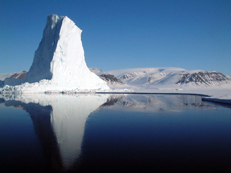 This beautiful image shows a unique looking iceberg in Greenland. There is a blue sky and the iceberg reflects off the cold water.