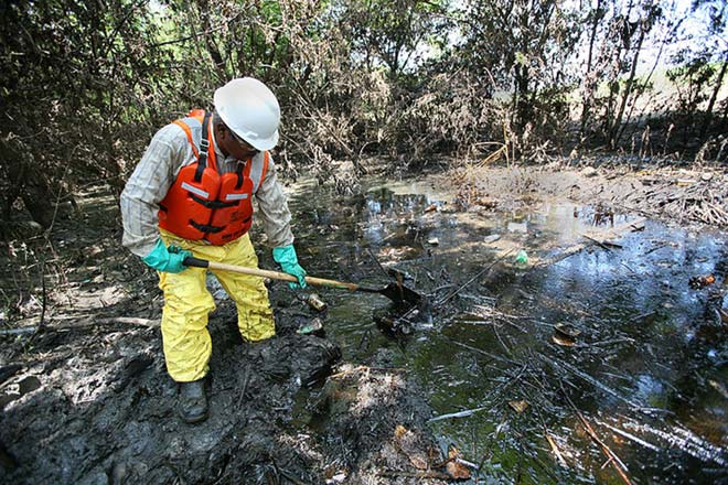 After flooding and oil contamination from a local refinery destroyed much of a nearby town, a contractor works hard to continue the oil spill cleanup job.