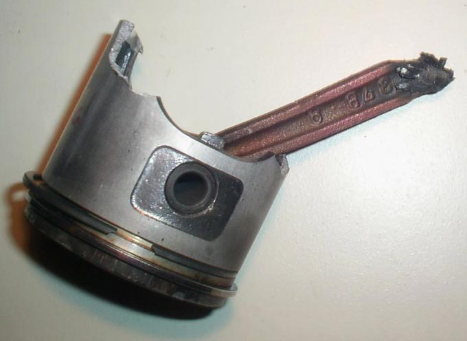 This picture shows a broken piston and connecting rod from a scooter.