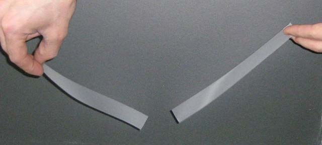 This image demonstrates the force of attraction between oppositely charged objects, in this case two pieces of tape.
