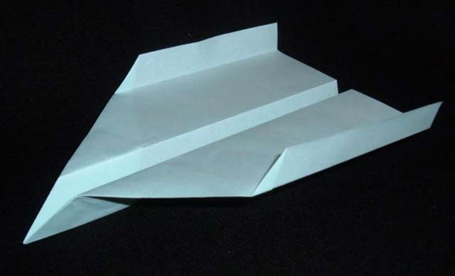 This image shows a well designed paper plane with clean folds set against a black background.