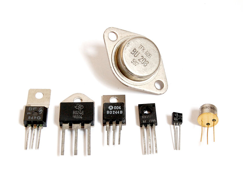 This photo shows a close up of seven different transistor types set against a white background.