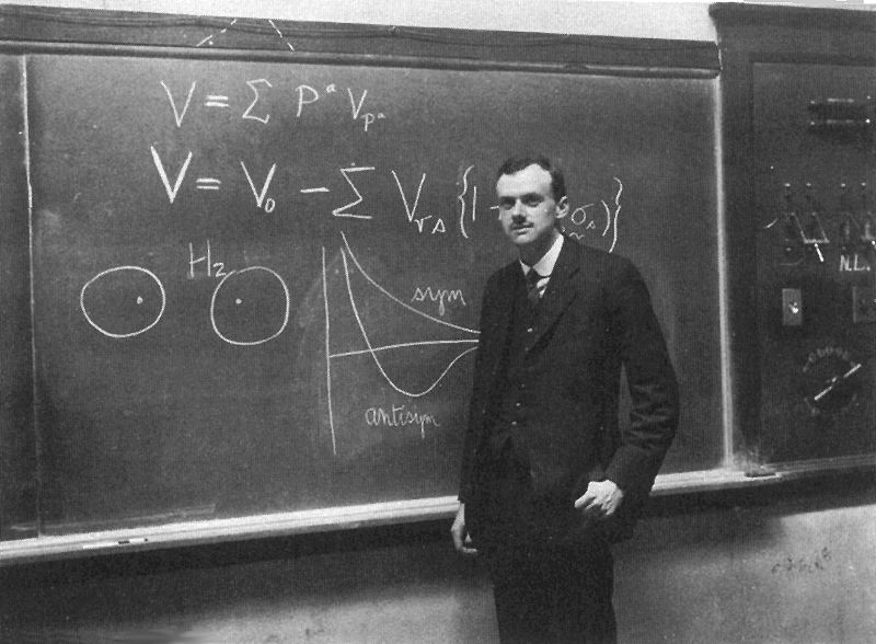 This photo shows British theoretical physicist Paul Dirac standing in front of a blackboard. Dirac made many contributions in the early development of quantum mechanics.