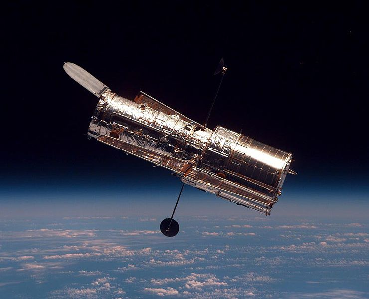 A clear photo of the famous Hubble Space Telescope with Earth and space in the background.