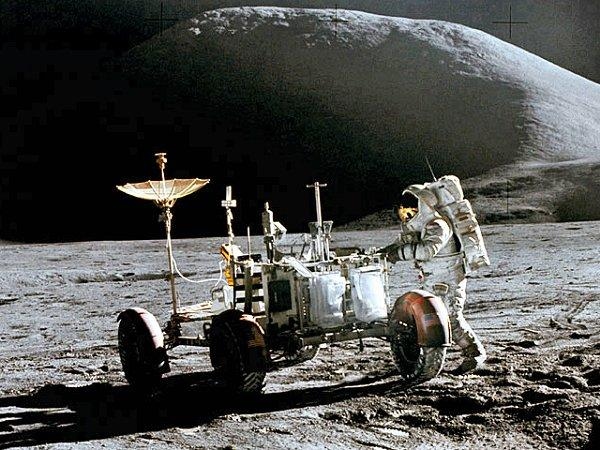 A photo of an astronaut as he interacts with a lunar rover while on the moon.