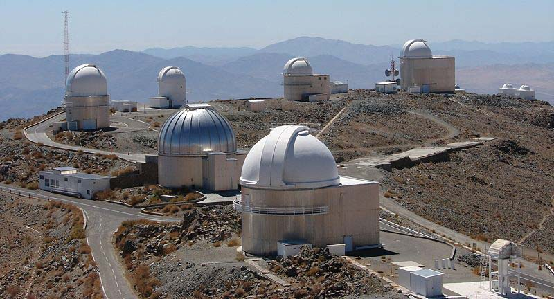 A photo taken on a fine day showing a number of telescope domes at an observatory.
