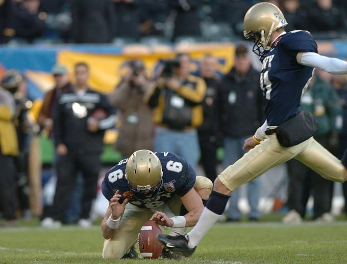An American football kicker lines up his kick attempt as he makes his final stride before kicking the ball. His team mate holds the ball in position to help make the kick as accurate as possible.