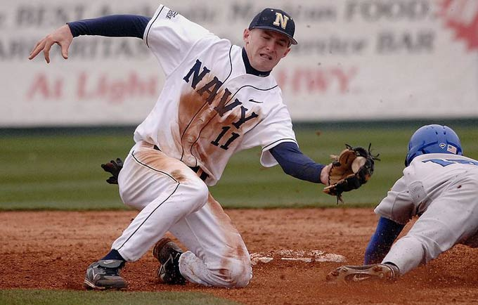 A baseball player leans in to make a tag on an opposing player as he slides in to the base.