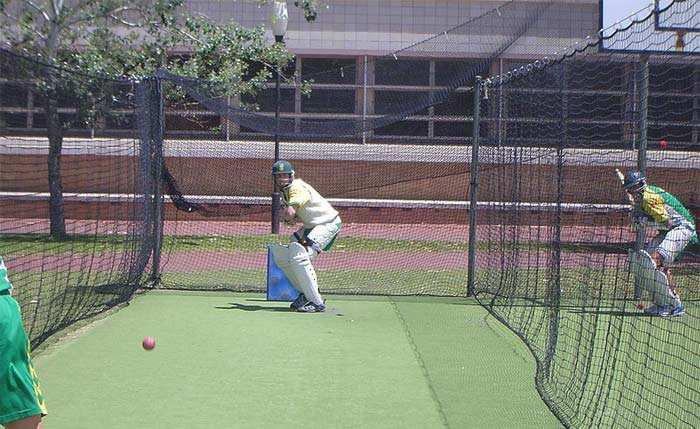 Two batters from the South African cricket team practice in the nets, facing deliveries from their team mates.