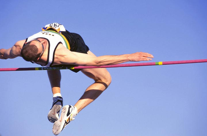 An athlete leaps high into the air and clears the bar while competing in a high jump competition.