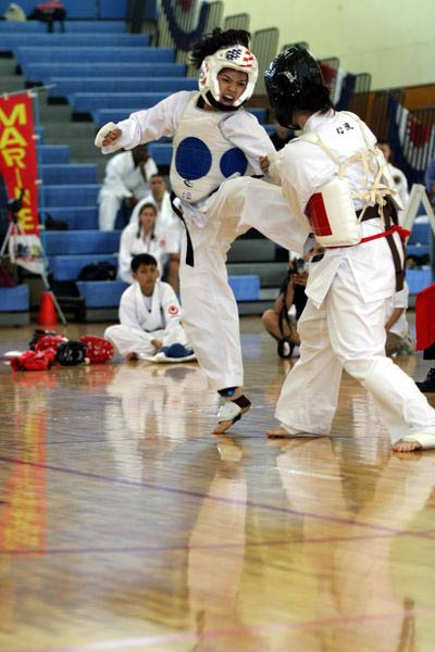Two karate competitors battle it out in a competition, one defends herself as the other makes an attacking kick.