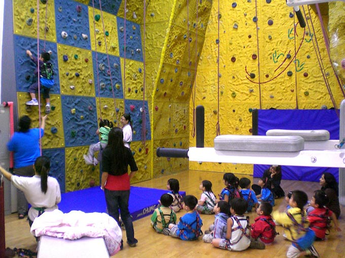 This photo shows a group of children learning how to climb on a kids climbing wall. The walls are brightly colored and feature a large number of holds and possible routes to make the challenge manageable for beginners and the inexperienced.
