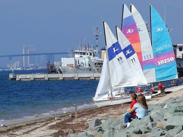 A group of small sailing boats sit on the sand on a beautiful sunny day.