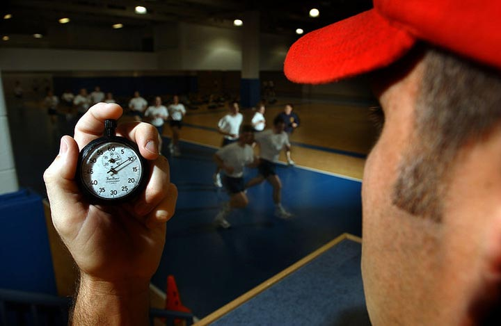 A trainer monitors the progress of a group as they run inside a gymnasium. The trainer is timing them using a stopwatch which can be seen in the image foreground.