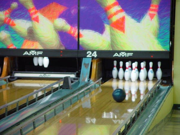This bowling photo shows a bowling ball as it rolls down the lane towards the pins.