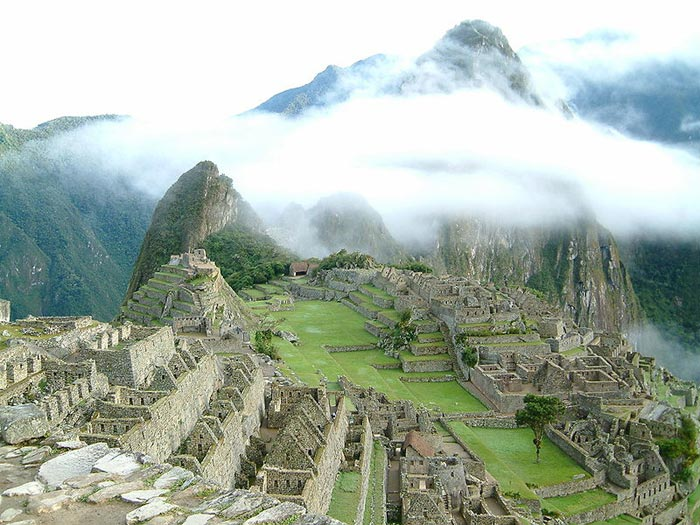 Machu Picchu is a famous Inca site found deep in the mountains of Peru. Sometimes known as 'The Lost City of the Incas', it was largely unknown by the outside world until it was brought to international attention in 1911 by Hiram Bingham, an American historian. It is now a popular tourist destination with many people trekking through the mountains to reach the famous landmark every year. This photo shows the famous location of Mach Picchu sitting amongst white clouds.