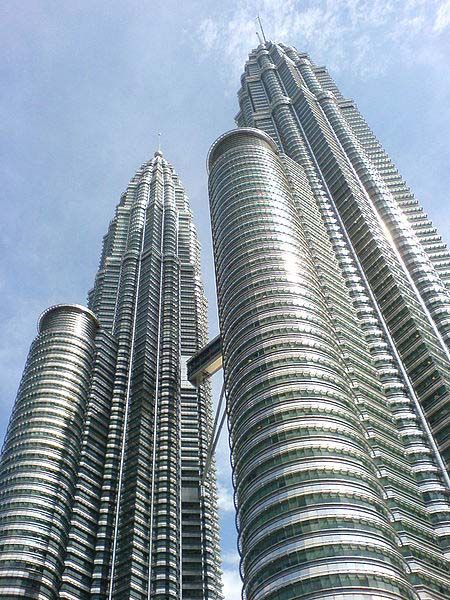 This photo is taken from the ground looking up at the impressive Petronas Towers in Kuala Lumpur, Malaysia. The twin buildings were once the tallest in the world but still remain among the tallest. They reach an incredible 452 metres (1483 feet) in height and feature 88 floors.