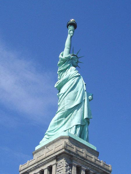 This photo looks up at the famous Statue of Liberty that is located on Liberty Island, in the harbor of New York, USA. The well known statue was gifted to the United States by the French as a gift to commemorate the one hundred year anniversary of the signing of the Declaration of Independence.