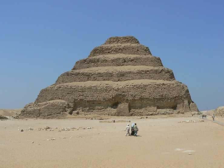 This photo shows the Step Pyramid of Djoser on a beautiful sunny day near the city of Memphis in Egypt. The pyramid stands 62 metres (203 feet) tall. Its immense size can be clearly seen when contrasted against the seemingly small people walking in front of and beside the giant landmark.