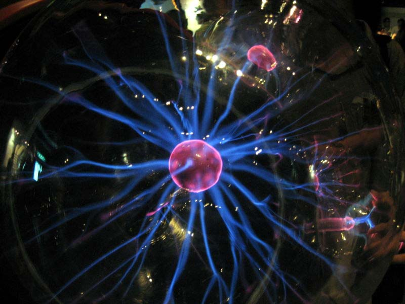 This close up photo shows a plasma ball in action while being contained inside a spherical case.