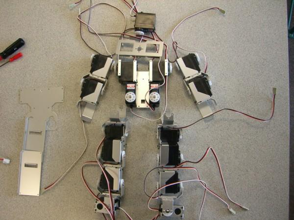 This photo shows a view looking down on a number of robot parts that combine to make a programmable robot that can perform complex movements. Some of the visible parts include wires, servo motors and metal brackets.