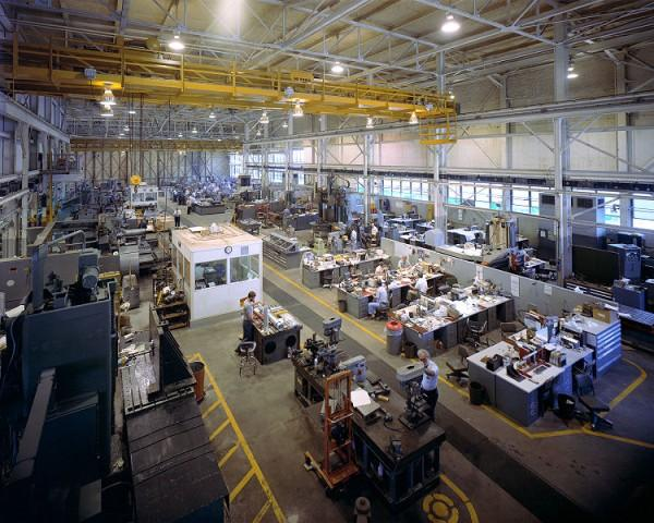 A large number of people can be seen hard at work in a large technology laboratory. The workers design and manufacture various technologically advanced products for use in various industries.