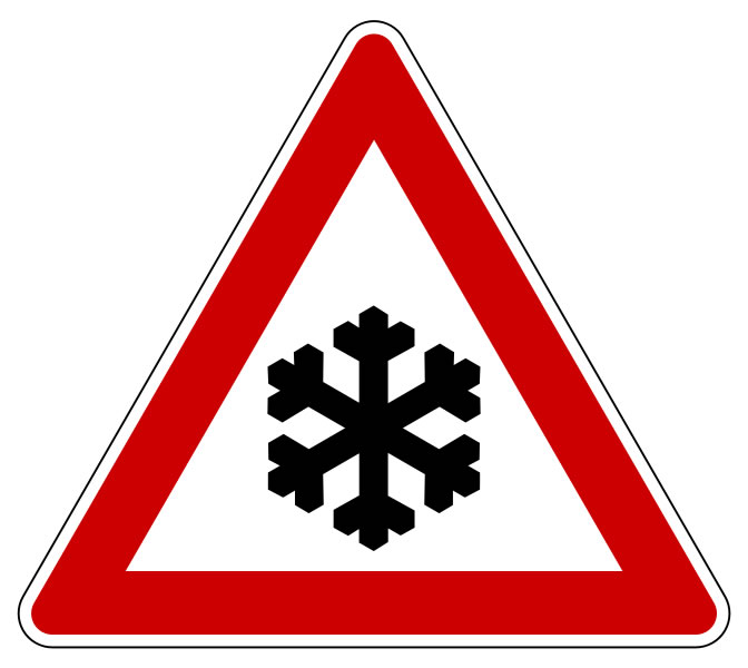 This snow warning sign is used to alert people of possible snow dangers in the area. This risk can be particularly dangerous for those traveling in vehicles. The sign features a black snowflake inside a red triangle.