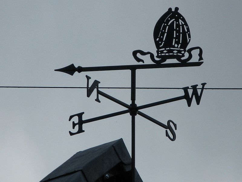 A weather vane can be seen on top of a house roof. It shows the letters N, S, E, W which represent north, south, east and west. It is used for wind direction.